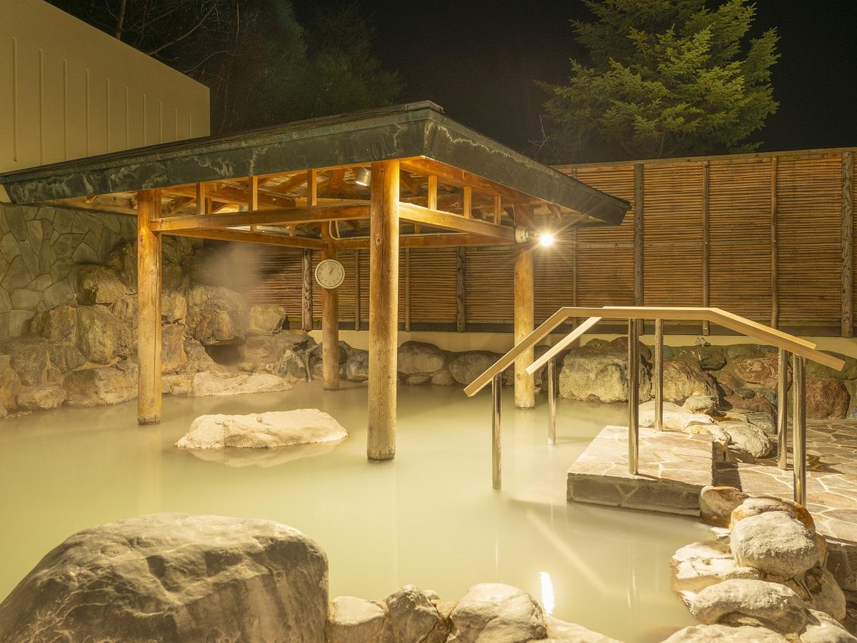 【夜の露天風呂】白濁の湯がライトに照らされて、幻想的な雰囲気に。夜のひとときを楽しんで!